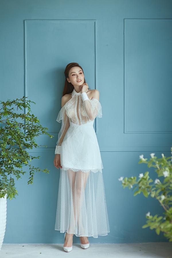 Đầm khoét vai thêm phần gợi cảm nhờ cách phối hợp khéo léo các chất liệu vải xuyên thấu, vải ren và lụa đồng sắc trắng.