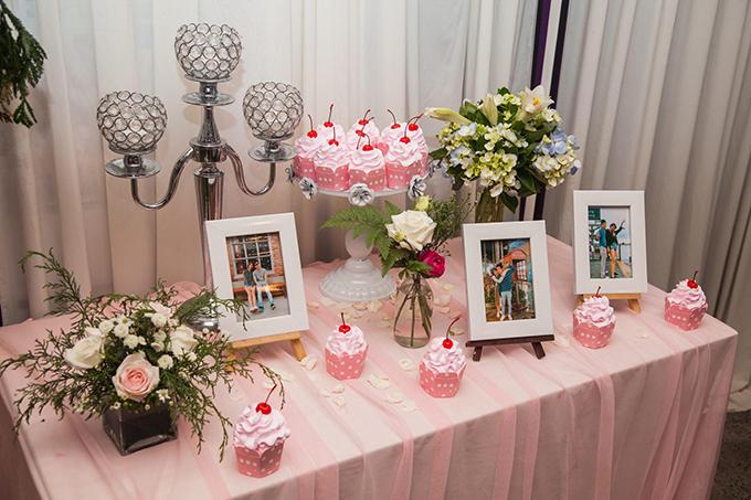 Uyên ương trang trí bàn tiếp tân bằng vải tuyn phớt hồng, giá nến, bức hình của cả hai và những chiếc bánh cupcake với quả cherry hồng xinh xắn.