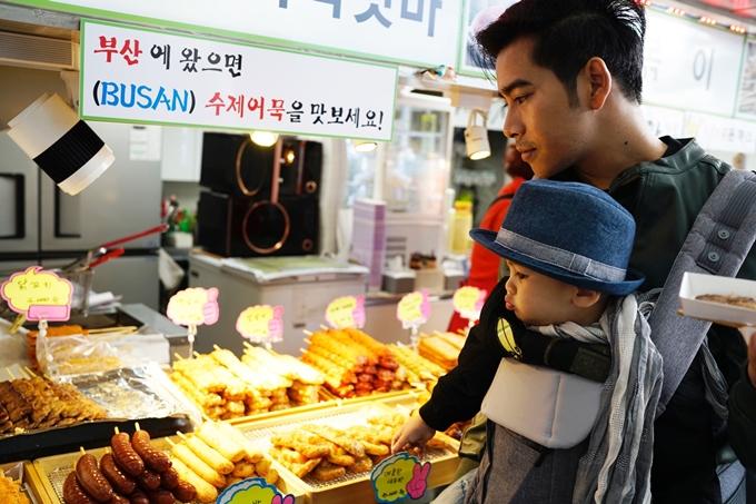 Cậu nhóc tỏ vẻ hào hứng trước các món ăn đường phố khi được bố bế vào một gian hàng.