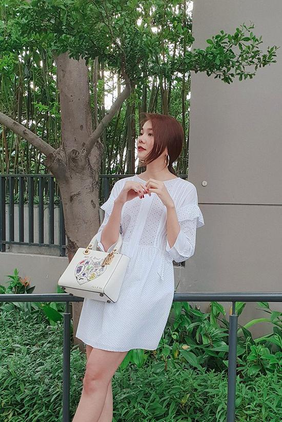 Thanh Hằng mix đồ ton - sur - ton với váy trắng họa tiết cắt hoa laser đi kèm túi của Dior.
