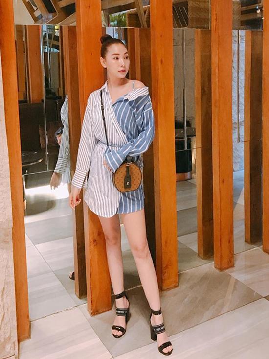 Quỳnh Thư khoe chân dài với bộ đầm sơ mi trễ vai gợi cảm.Ngoài mẫu sandal kiểu dáng độc đáo, người đẹp còn chọn thêm chiếc túi Petite Boite Chapeau của Louis Vuitton làm điểm nhấn.