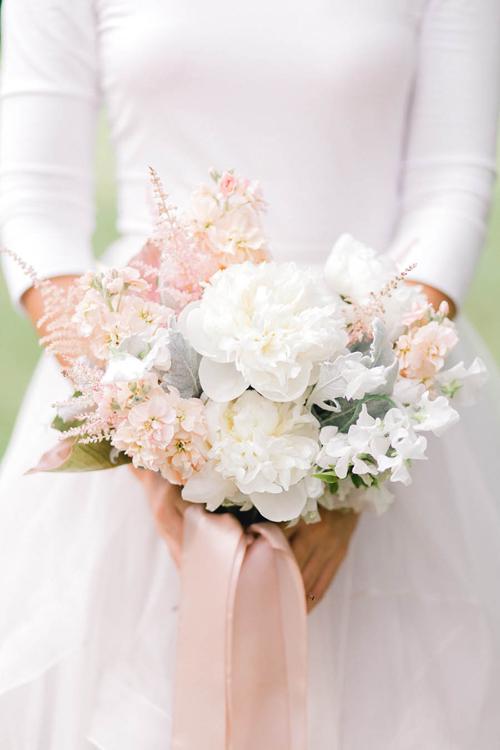 Hoa cầm tay của cô dâu mang sắc trắng chủ đạo của những bông mẫu đơn cỡ lớn, trên nền của lá cỏ, hoa phi yến và hoa bụi nhỏ.