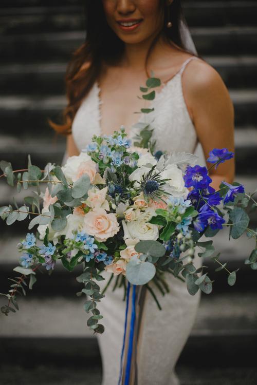 Cô dâu chọn hoa cưới cầm tay cùng tông xanh dương để phù hợp với không gian làm lễ.