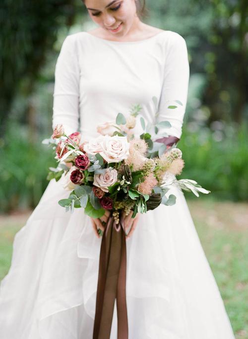 Hoa của cô dâu được kết từ những bông hồng màu kem nhạt, đỏ tía và độc đáo với các nhanh cỏ bông xù.