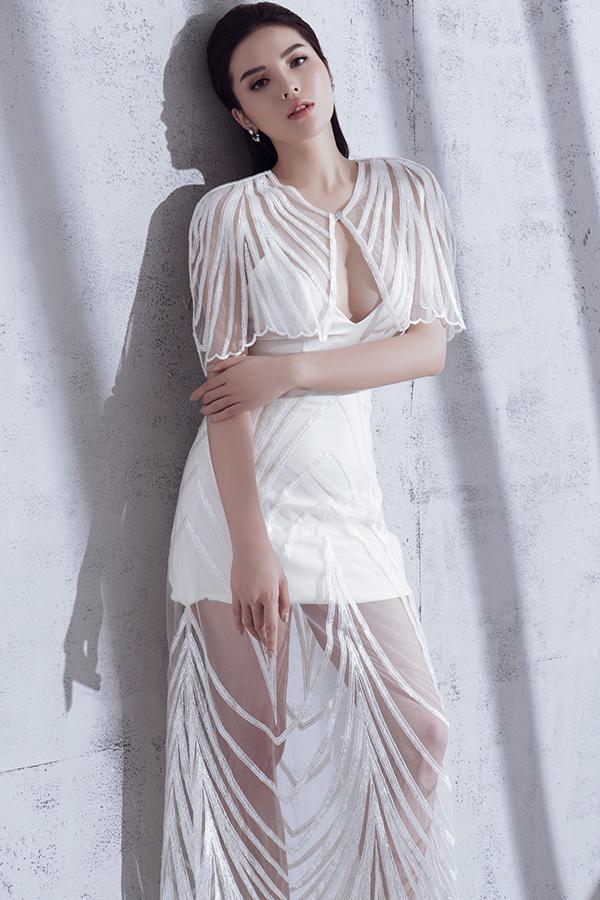Váy ngắn cúp ngực táo bạo trở nên ấn tượng hơn bởi cách phối vải lưới kèm hoạ tiết kẻ sọc ánh kim hài hoà cùng màu váy.