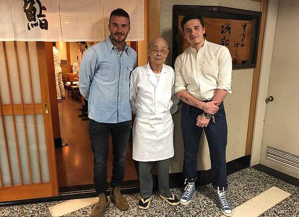 Hình ảnh đầu tiên nhìn thấy bộ đôi cha-con trai ngồi ở quầy của nhà hàng nổi tiếng, trong khi đầu bếp Jiro Ono chuẩn bị các món ăn phía sau quầy bar.