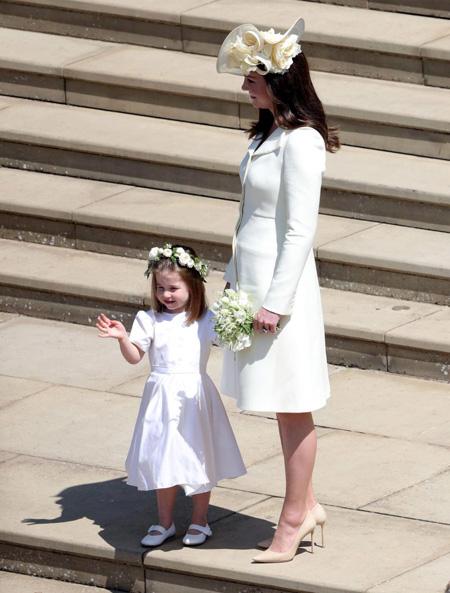 Kate nắm tay công chúa Charlotte trước nhà nguyện St George hôm 19/5. Cô bé 3 tuổi vẫy tay chào khi người hâm mộ khi cỗ xe chở vợ chồng Harry bắt đầu xuất phát đi quanh thị trấn Windsor. Ảnh: PA.