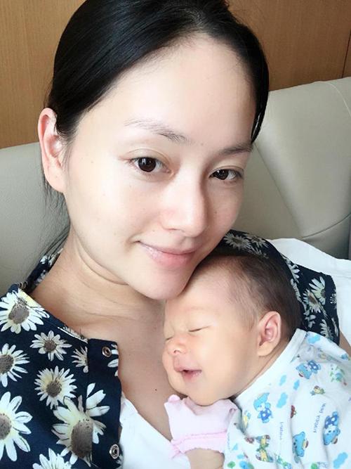 Nữ diễn viên ôm con gái vào lòng và chia sẻ: Ngủ trên ngực mẹ, chắc em đang mơ gì thích lắm nên cười tươi. Mẹ thì trông rõ là thiếu ngủ.