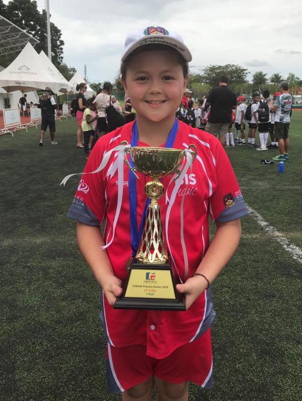 Bé Edwards khoe chiếc cúp mới giành được sau giải đấu ở Thái Lan.