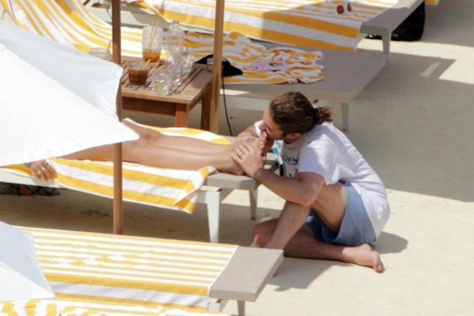 Bạn trai dịu dàng hôn chân Rita trong khi cô nằm phơi nắng và đọc sách.