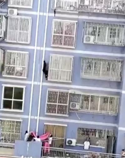 Cư dân trong tòa nhà dăng bạt ở tầng 1 đề phòng Zhang bị ngã khi tay không trèo lên tầng 5. Ảnh: Pear Video.