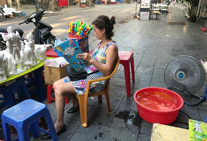 Một phụ nữ lao động trên hè phố chống nóng bằng cách sáng tạo chiếc quạt hơi nước từ thau chứa đá lạnh và chiếc quạt điện đơn sơ.