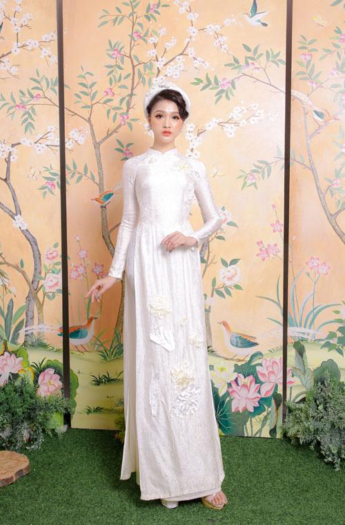 Mẫu áo dài lụa trắng họa tiết thêu hoa sen cùng màu gợi sự liên tưởng đến trang phục của các cô gái Hà thành xưa. Tuy nhiên, phom áo được may chiết eo gọn gàng, ôm sátbởi nàng dâu hiện đại luôn tự tin khoe đường cong cơ thểmột cách tinh tế.
