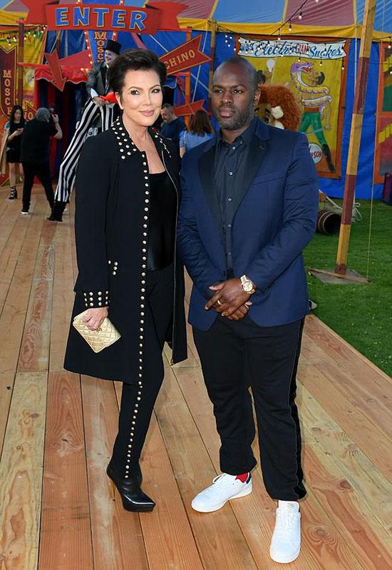 Kris Jenner diện cả cây đen nổi bật với đinh tán kim loại, tạo dáng bên phi công trẻ Corey Gamble tại sự kiện thời trang của Moschino. Show diễn được thiết kế giống như một rạp xiếc đủ sắc màu sinh động.