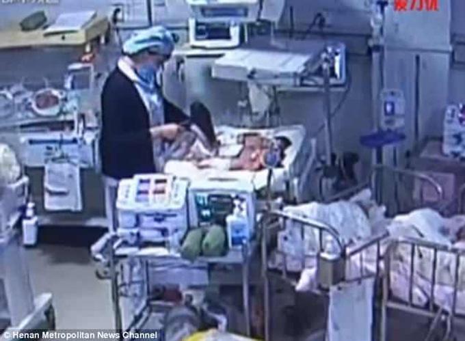Nữ y tá dùng máy sấy tóc sấy khô em bé nhưng bất cẩn để nó chĩa vào chân bé khi vẫn chưa tắt. Ảnh: Henan Metropolitan News Channel.
