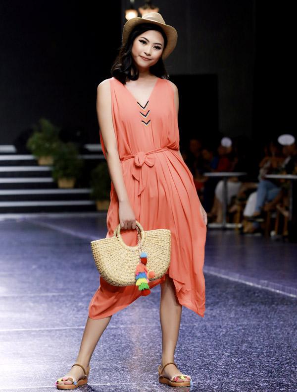 Người mẫu Đào Hà giới thiệu một mẫu váy dạo biển màu cam nổi bật.