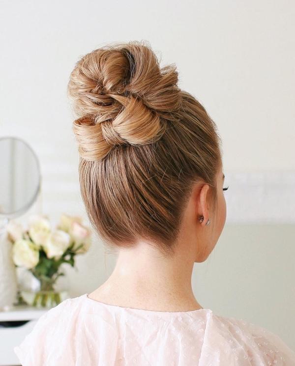 Kiểu 6: Từ kiểu tóc số 5, bạn có thể biến tấu bằng cách chừa ra hai lọn tóc phía dưới cùng của đuôi tóc, thắt thành nơ phía dưới búi tóc.