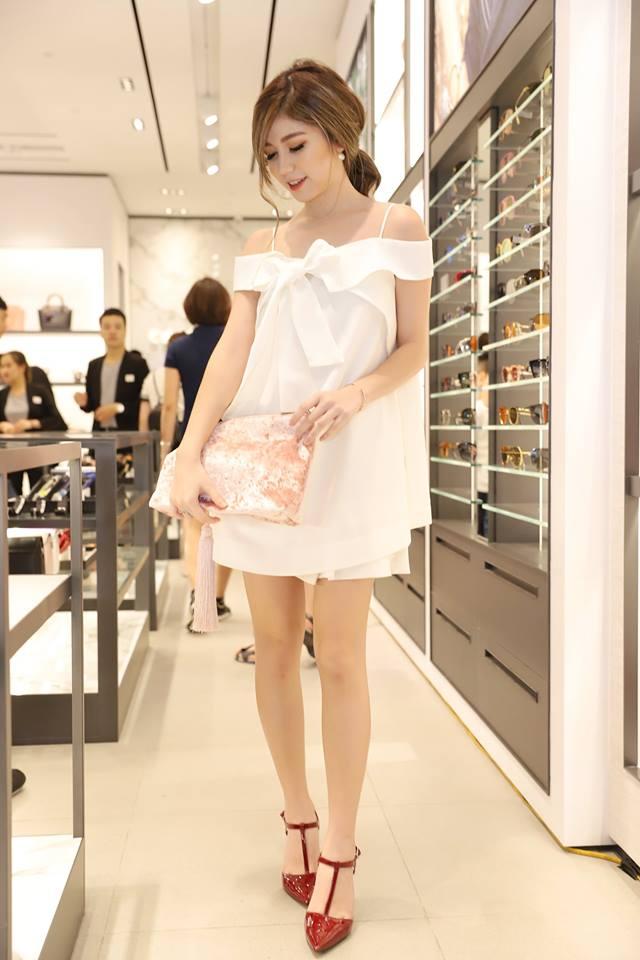 Người đẹp khéo léo phối chiếc đầm trắng trễ vai với mẫu túi clutch nhung hồng ấn tượng.