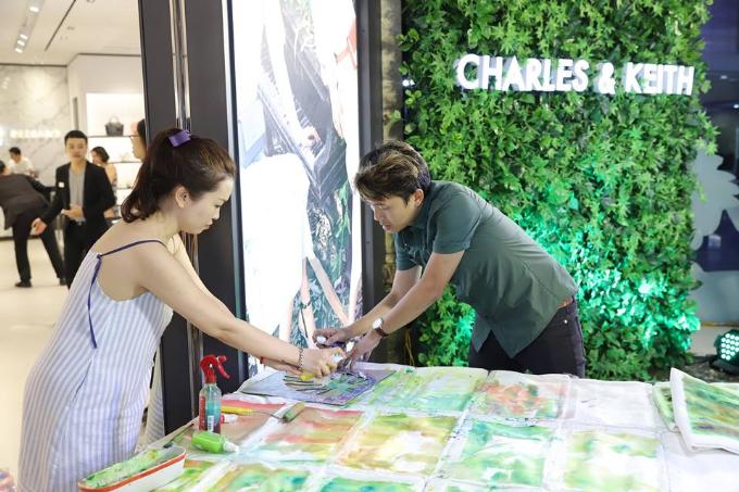 Họa sĩ vẽ art paiting lên túi tote ngay tại cửa hàng dành tặng khách dự sự kiện.