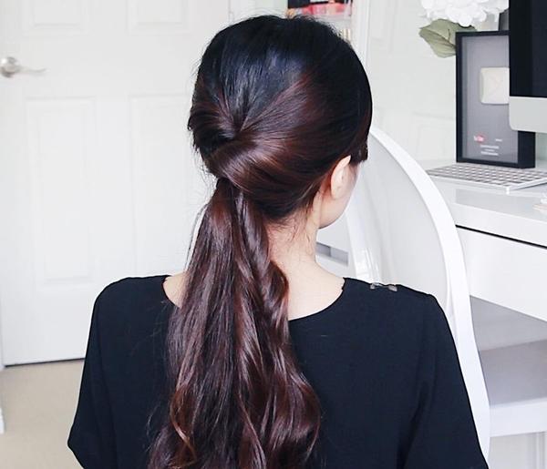 Kiểu 1: Buộc tóc đuôi ngựa thấp sau đó tẽ đôi phần tóc phía trên nút buộc, cuộn đuôi tóc qua kẽ hở đó.