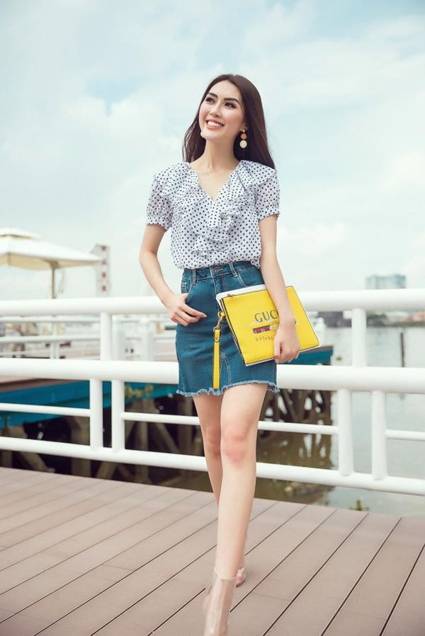 Phong cách trẻ trung cho nàng công sở sành điệu với áo bèo nhún đi cùng chân váy jean, clutch tông màu nổi và bốt nhựa trong.