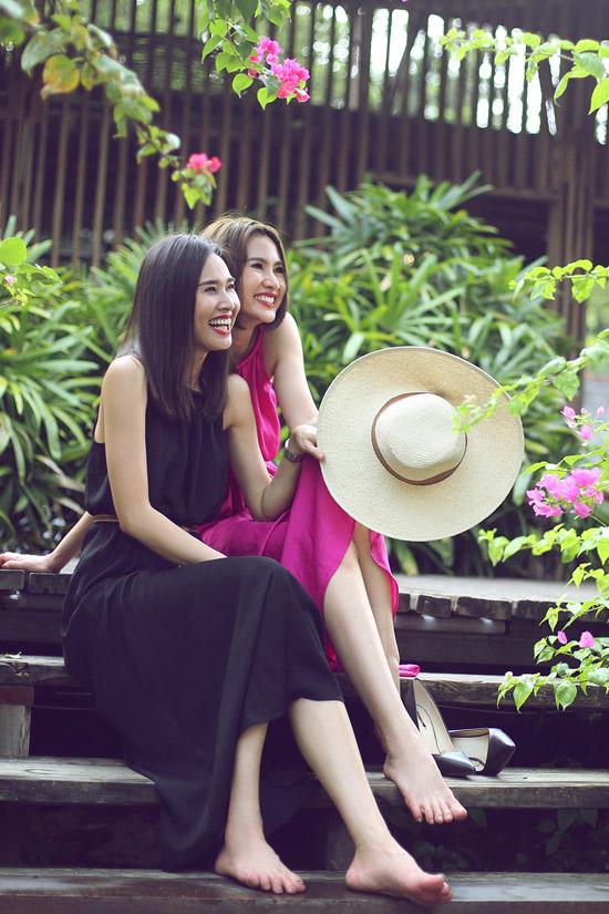 Cả hai chọn váy có màu sắc đối lập, trang điểm nhẹ nhàng và khoe nụ cười tỏa nắngtrong không gian xanh mướt của một khu resort.