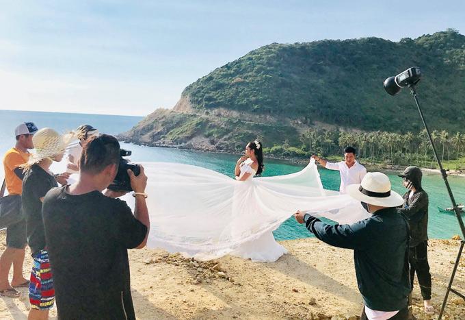 Ông xã cùng các thành viên trong êkíp chụp ảnh cưới hỗ trợ để Thu Thảo có bức ảnh bay bổng giữa thiên nhiên.