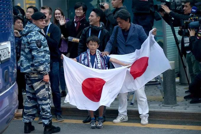 Một fan nhí cầm cờ chào đón đội tuyển Nhật Bản đặt chân đến Nga.