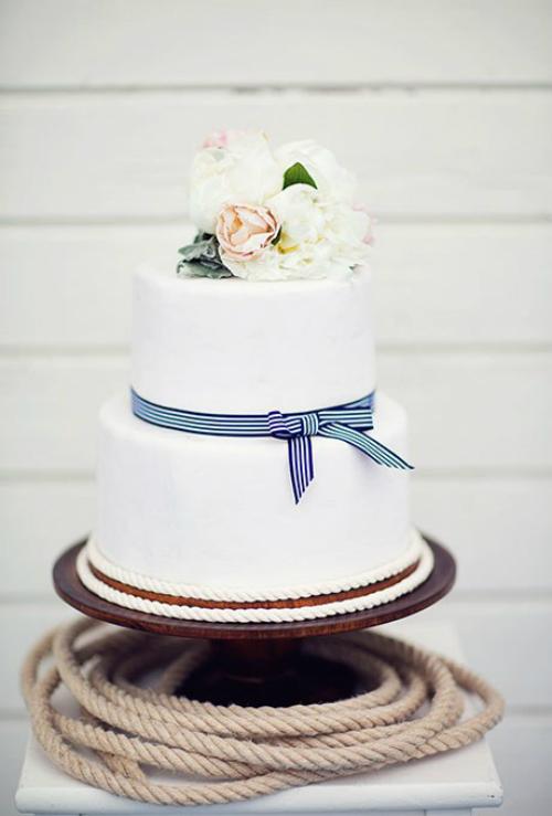 Một chiếc ruy băngtrắng sọc xanh được thắt nơtrên chiếc bánh cưới sẽ phù hợp với các đám cưới tổ chức ngoài bãi biển. Đồng thời, bạn có thể trang trí thêm sợi dây thừng để gợi nhắc về chủ đề biển cả.
