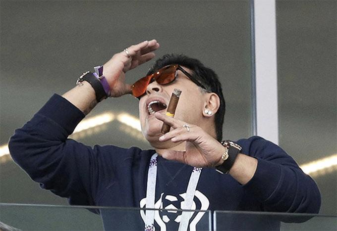 Trên tay Maradona cầm một điếu xì gà.