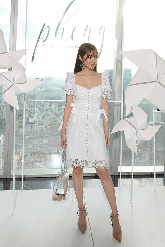 Quỳnh Hương chọn túi nhựa trong cùng váy trắng trang trí nút cài hạt ngọc trai điệu đà khi đến xem show.