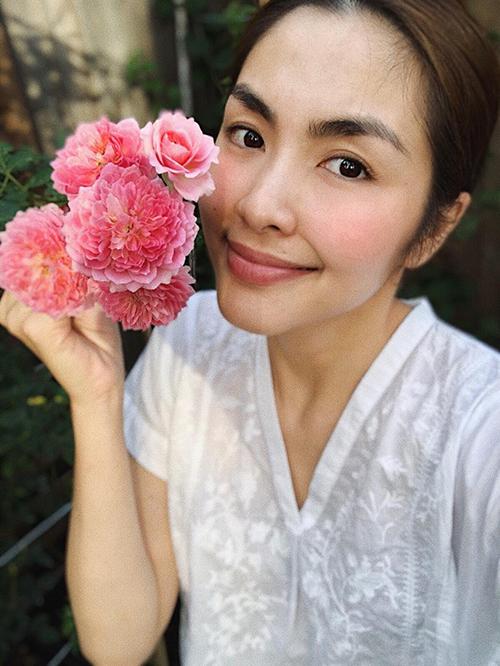 Tăng Thanh Hà ra vườn ngắm hoa hồng - thành quả chăm sóc của cô sau một thời gian. Khi ở nhà, cô ăn mặc giản dị và để mặt mộc.