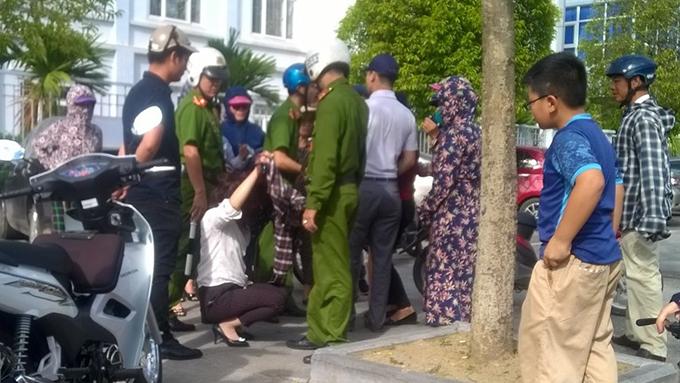 Cô gái trẻ (ngồi) phải nhờ cảnh sát can thiệp mới thoát trận đòn đánh ghen trên phố. Ảnh: Lam Sơn.