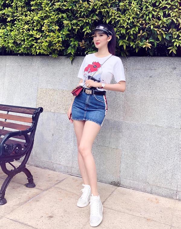 Ngọc Loan The Face sành điệu với cách chọn mũ lưỡi trai nhựa trong phối cùng túi mini, chân váy jean kẻ sọc, áo thun họa tiết và giầy sneaker.