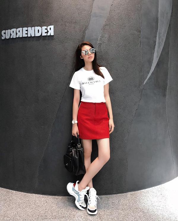 Jolie Nguyễn phối 3 tông màu trắng, đỏ, đen ăn ý trên set đồ gồm áo thun hàng hiệu, giầy thể thao, chân váy kẻ sọc và túi xách hàng hiệu.