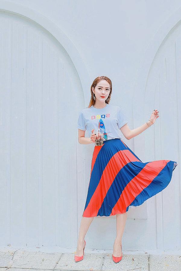 Chân váy dập ly rực rỡ sắc màu là trang phục được Minh Hằng chọn lựa phối cùng áo thun, giày mũi nhọn hài hòa về màu sắc.