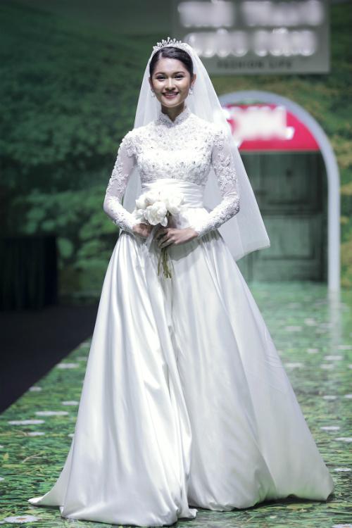 1. Váy cưới chữ A: Á hậuThùy Dung mở màn show diễn thời trang vừa diễn ra với kiểu váy cổ điển, thanh lịch. Nhà thiết kế lấy cảm hứng từ hoàng gia để tạo nênmẫu váy với thiết kế cổ trụ thêu ren nổi.