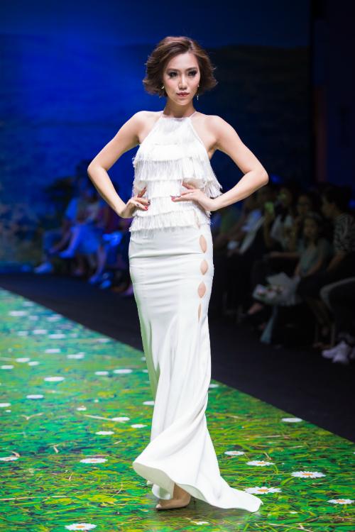 Váy có cổ yếm tua rua xếp nếp vànhững khoảng cut out đứt quãngtừ eo đến ngang đùi tạo nên nét khác biệt.