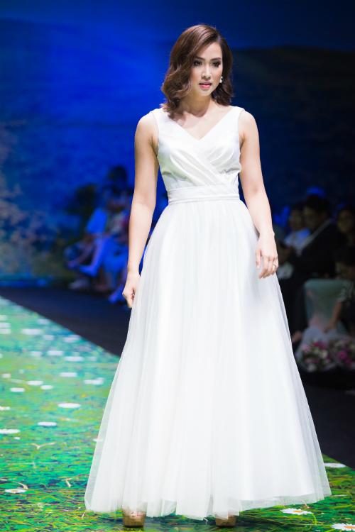 Cô dâu diện váy có thiết kế cổ chữ V đơn giản với phần chân váy là lớp vải tuyn mỏng manh.