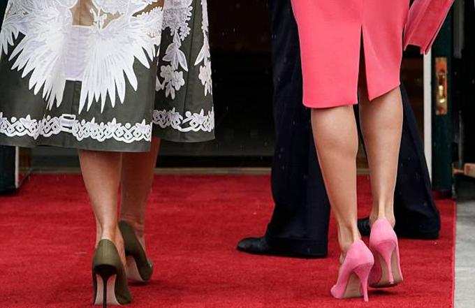 Bà Melania diện chiếc váy màu trắng và oliu của thương hiệu Valentino kết hợp giày cao gót cùng màu, trong khi Hoàng hậu Letizia diện mẫu đầm ôm màu hồng của Michael Kors, giày và ví cầm tay cũng màu hồng.