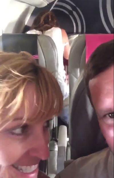 Đôi vợ chồng trung niên giơ điện thoại lên cao để quay cảnh làm tình của hai thanh niên trẻ trên máy bay. Ảnh cắt từ video.