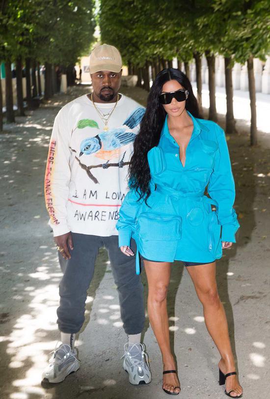 Kim Kardashian được ông xã Kanye West hộ tống tới xem show Louis Vuitton trong khuôn khổ Tuần lễ thời trang Paris ngày 21/5. Cặp sao diện đồ phong cách với tông màu xanh và xám.
