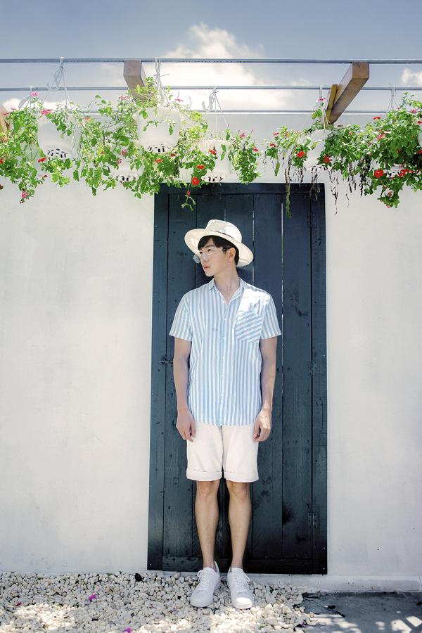 Sơ mi kẻ sọc xanh trắng được phối hợp nhịp nhàng cùng short, giầy sneaker và mũ fedora.