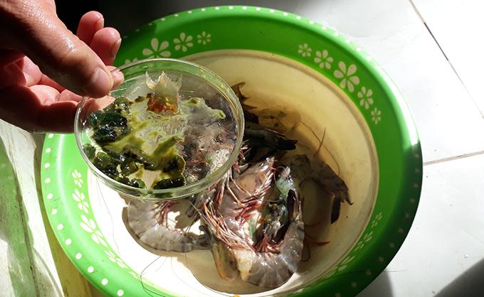 Tạp chất màu xanh được lấy ra từ thân những con tôm trong cửa hàng hải sản ở Sầm Sơn.