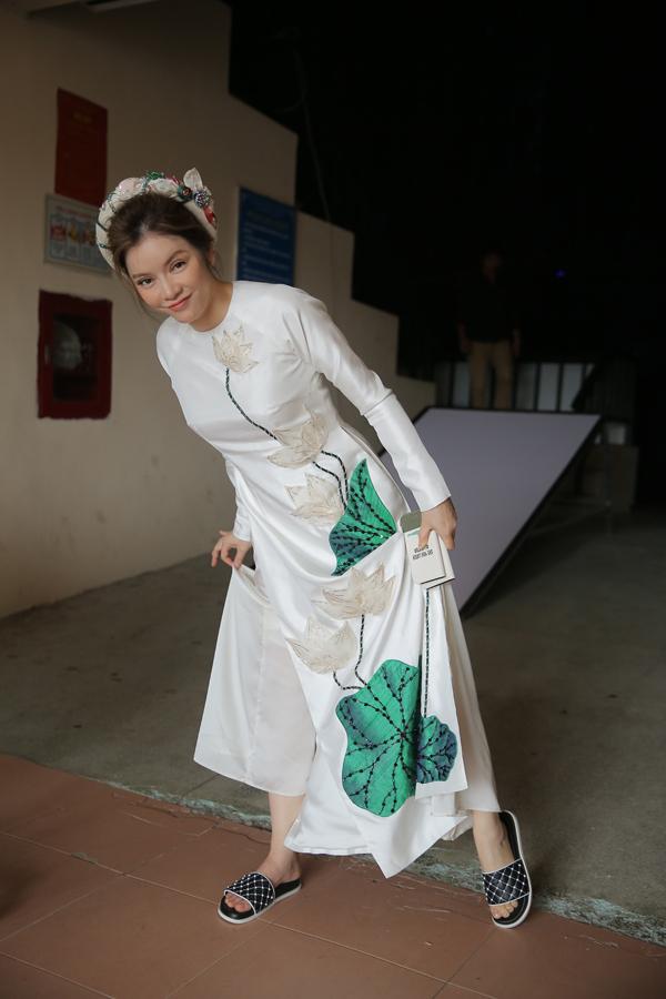 Tại hậu trường, nữ diễn viên đi dép lê để dễ di chuyển. Cô liên lục phải túm quần và tà váy để bộ trang phục không bị quét đất.