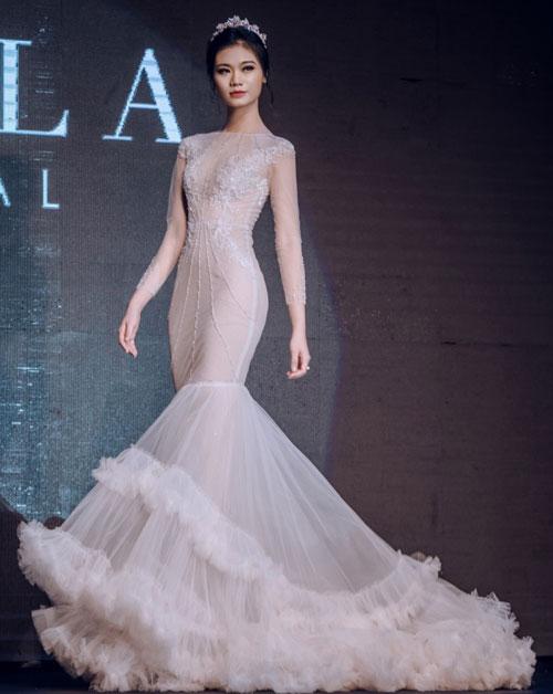 Chiếc váy cưới đuôi cá có phần chân tạo dáng bồng bềnh với những lớp vải lưới. Thiết kế lấy cảm hứng từ những cơn sóng biển mùa hè.
