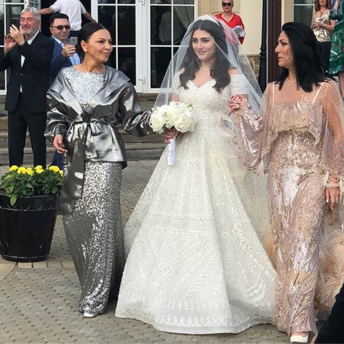 Vương miện của cô dâu cũng được gắn đá quý và kết hợp cùng khăn voan trơn.
