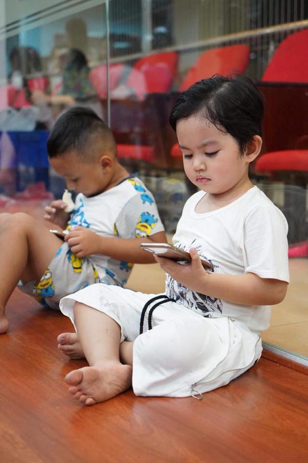 Sau khi mệt vì chạy nhảy,cậu nhóc ngồi một góc xem phim hoạt hình trên điện thoại.