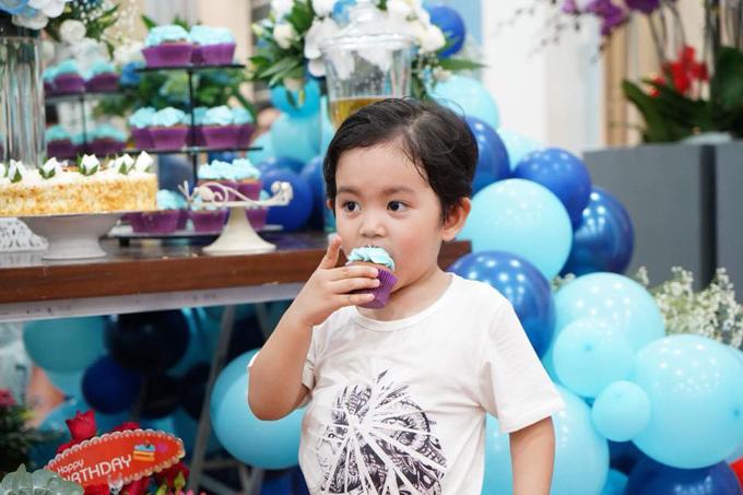 Cậu nhóc 3 tuổi lém lỉnh ăn bánh mà không quan tâm đến mọi người xung quanh.
