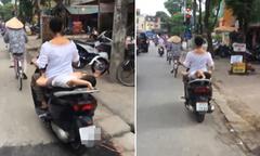 Mẹ đầu trần chở con nhỏ nằm ngửa trên xe máy